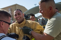 "Master Sgt. Alex, 380th Expeditionary Civil Engineering Squadron First Sgt., laughs with fellow firefighters after completing a timed firefighter confidence course at an undisclosed location in Southwest Asia, Jan. 16, 2016. ""This brings everybody together and makes everyone work as a team,"" Alex said. ""It doesn't matter who you are or what shift you work. Once you get in that suit everybody is cheering for you.""   (U.S. Air Force photo/Senior Airman Tyler Woodward)"