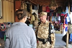 First Sgt. (Plutonier-major) Victor Balan walks a presence patrol at one of the local national bazaars on Bagram Airfield.  Balan talks with the shop keepers and patrons and keeps a keen eye out for any unusual activities or conditions.  The checks are routine requirements for a typical Provost Marshall military police patrol.  Balan is a member of the 4th Romanian Military Police Detachment from the Romanian Land Forces 265th MP Battalion, in Bucharest.