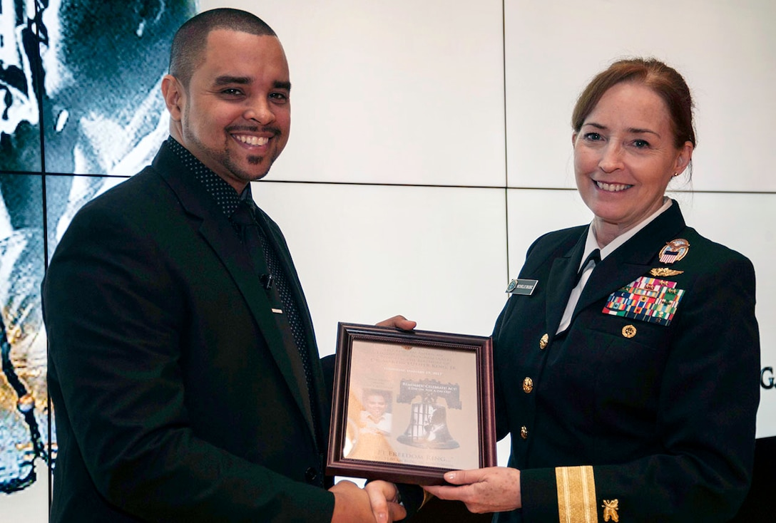 DLA Land and Maritime Commander Navy Rear Adm. Michelle Skubic (right) presents Pastor John T. Boston, II with a framed poster from the Defense Supply Center Columbus Dr. Martin Luther King Jr. observance ceremony. The Jan. 19 event celebrated the life and legacy of Dr. King with music, dance, and a presentation by Pastor Boston.