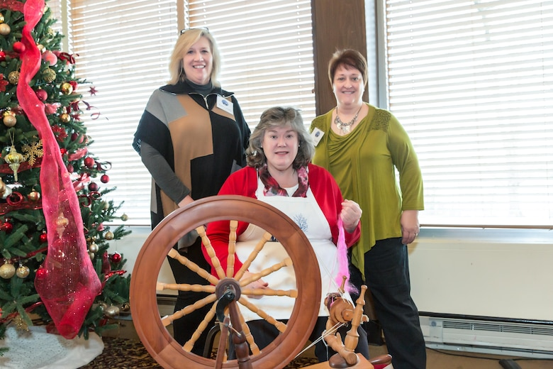 Jane Lovett (center), co-owner of Falls Mill, spins yarn while presenting information about the mill at the AEDC Woman's Club meeting Jan. 5 at the Arnold Lakeside Center. Pictured with Lovett are AEDCWC members Kate Canady, left, and Anne Wonder. (Courtesy photo)