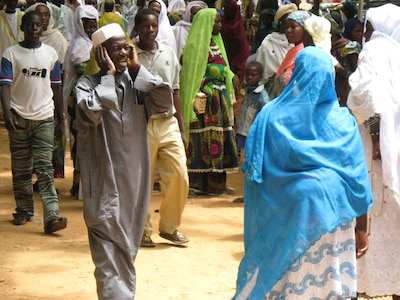 A man sings religious songs among the crowd at a religious event in rural Niger.