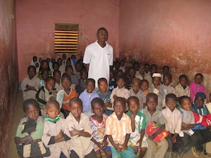 "A teacher and his students at a state-sponsored ""Franco-Arabic"" school or madrasa in Niger. Such schools teach in both French and Arabic and are highly popular with parents in the Sahel."