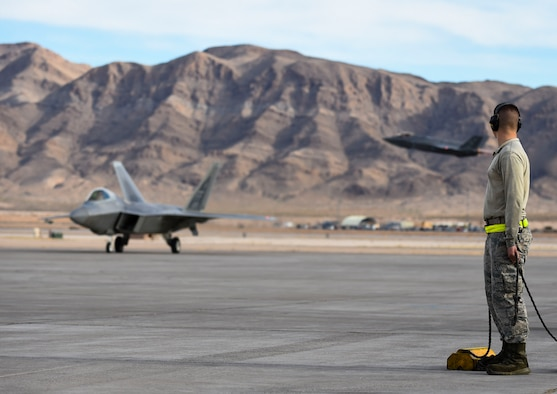 U.S. Air Force Airmen with the 1st Aircraft Maintenance Squadron prepare to taxi F-22 Raptor at Nellis Air Force Base, Nev., Feb. 18, 2017. The aircraft assigned to  Langley Air Force Base, Va.'s, 1st Fighter Wing will conduct air combat training sorties with various aircraft including the F-35 Lightning II during Red Flag 17-1. (U.S. Air Force photo by Staff Sgt. Natasha Stannard)