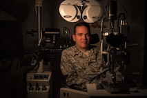 Maj. Scott Martin, 23d Aerospace Medicine Squadron optometry flight commander, poses for a photo with various pieces of optometry equipment, Jan. 19, 2016, at Moody Air Force Base, Ga. Optometrists are responsible for examining, diagnosing, treating and managing diseases and disorders of the visual system. In the Air Force, there are currently 136 active duty, 74 Air Force reservist and 90 Air National Guard optometrists. (U.S. Air Force photo by Airman 1st Class Daniel Snider)