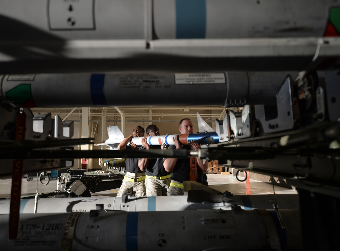 U.S. Air Force Staff Sgt. Christopher A. Holmes, Senior Airman Michael B. Cheek and Airman 1st Class Elijah Cruz, 43rd Aircraft Maintenance Unit aircraft armament systems technicians remove a training missile from a holding platform to manually load into an F-22 Raptor at Tyndall Air Force Base, Fla., Jan. 20, 2017. The load crew was the first of four teams to compete for the 2016 Load Crew of the Year Award. (U.S. Air Force photo by Tech. Sgt. Javier Cruz/Released)