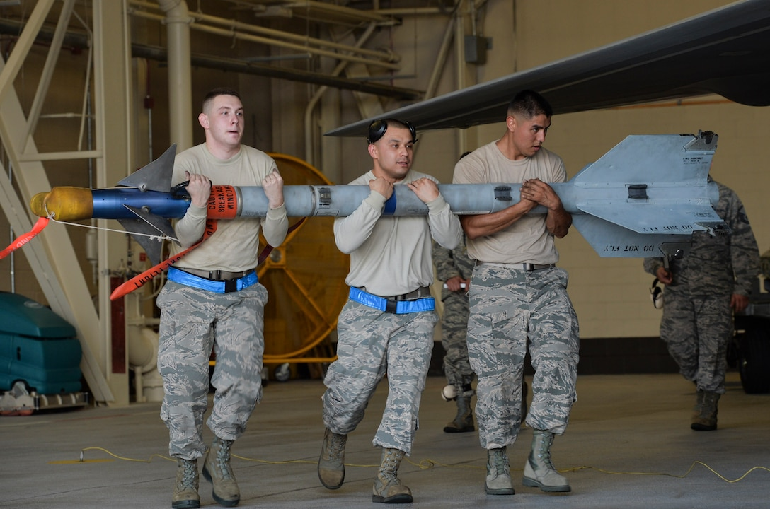 U.S. Air Force Staff Sgt. Vincent A. Miller, Staff Sgt. Michael A. Avalos and Senior Airman Jack T. Crane from the 95th Aircraft Maintenance Unit, carry a training missile to manually load into an F-22 Raptor during the Load Crew of the Year competition at Tyndall Air Force Base, Fla., Jan. 20, 2017. The teams of Airmen completed uniform inspections, a knowledge test and a 90 minute loading evaluation. (U.S. Air Force photo by Tech. Sgt. Javier Cruz/Released)