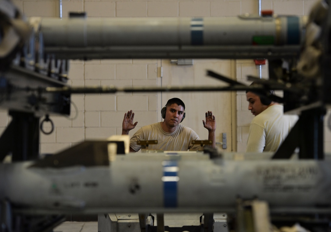 U.S. Air Force Staff Sgt. Michael A. Avalos, 95th Aircraft Maintenance Unit armament systems technician, raises his hands from the steering wheel of a munitions transportation vehicle to allow Staff Sgt. Vincent A. Miller, 95th Aircraft Maintenance Unit armament systems technician, to make adjustments to a loading arm at Tyndall Air Force Base, Fla., Jan. 20, 2017. The Airmen were evaluated on their ability to load weapon systems into an F-22 Raptor in a timely, safe and reliable manner under 90 minutes. (U.S. Air Force photo by Tech. Sgt. Javier Cruz/Released)