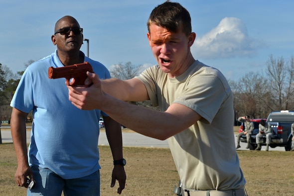 U.S. Air Force Airman 1st Class Austin Reese, 20th Security Forces Squadron entry controller, aims an artificial training weapon at a simulated attacker during his pepper spray training while Karl Johnson, 20th SFS trainer, motivates him to continue at Shaw Air Force Base, S.C., Jan. 18, 2017. During a use of force training day, Airmen reviewed less-lethal weapons, operational security and identification procedures, to include the new Real ID Act changes. Although some of the training was classroom-based, the Airmen also performed baton drills and situational use of force training. Team Shaw defenders who had not yet experienced pepper spray first-hand were required to complete an obstacle course while affected by the substance. (U.S. Air Force photo by Airman 1st Class Destinee Sweeney)