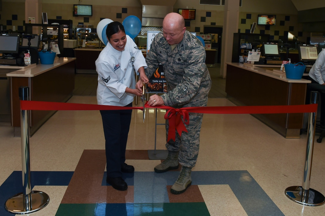 U.S. Air Force Col. William Brooks, 19th Mission Support Group commander, and Airman 1st Class Grethel Rodgers, 19th Force Support Squadron services apprentice, cut the grand re-opening ceremony ribbon Jan. 23, 2017, at the Hercules Dining Facility on Little Rock Air Force Base, Ark. The Hercules Dining Facility upgraded three sections to include the deli, pizza zone and grill. (U.S. Air Force photo by Staff Sgt. Kaylee Clark)