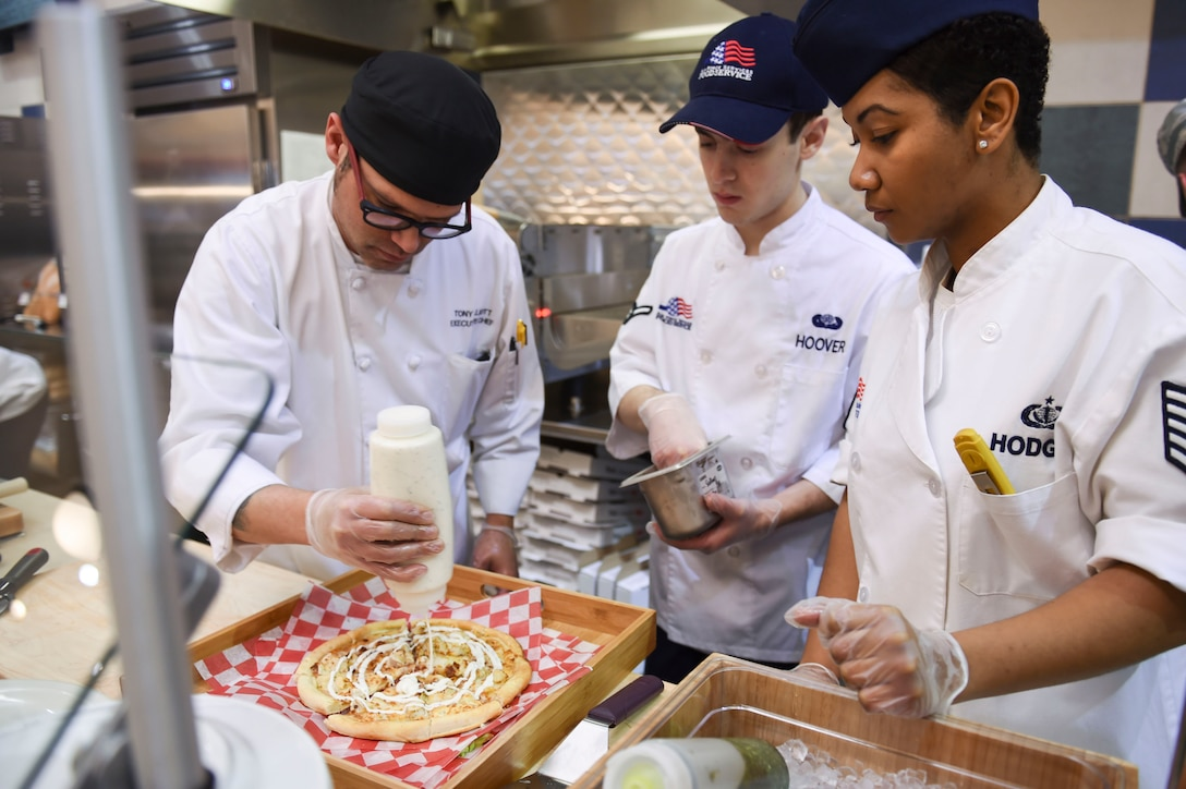 U.S. Air Force 19th Force Support Squadron dining facility Airmen and an Aramark chef prepare a personal-style pizza for sampling during the grand re-opening ceremony Jan. 23, 2017, at Little Rock Air Force Base, Ark. The pizza zone now offers made-to-order personal pan pizzas. (U.S. Air Force photo by Staff Sgt. Kaylee Clark)