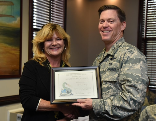 Col. C. Mike Smith, 81st Training Wing vice commander, presents Susan Frentz, Base Operations Support structure shop painter, the Environmental Dragon Award during the Energy Environmental Safety and Occupational Health Council Meeting at the 81st TRW headquarters building Jan. 18, 2017, on Keesler Air Force Base, Miss. Frentz received the award for managing an excellent hazardous materials program and for identifying products that will meet application and performance requirements while also being more eco-friendly. The Dragon Award is given by the base environmental office in recognition of outstanding performers. (U.S. Air Force photo by Kemberly Groue)