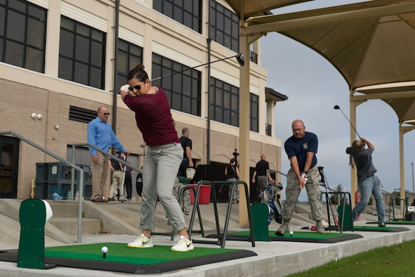 Danielle Nichols, wife of 1st Lt. Cody Nichols, 333rd Training Squadron student, prepares to hit a golf ball during the Power Tees driving range grand opening Jan. 20, 2017, on Keesler Air Force Base, Miss. The Power Tee is an automated ball teeing system aimed to help regular golfers improve their game and swing and to attract young golfers to the course. (U.S. Air Force photo by Andre' Askew)