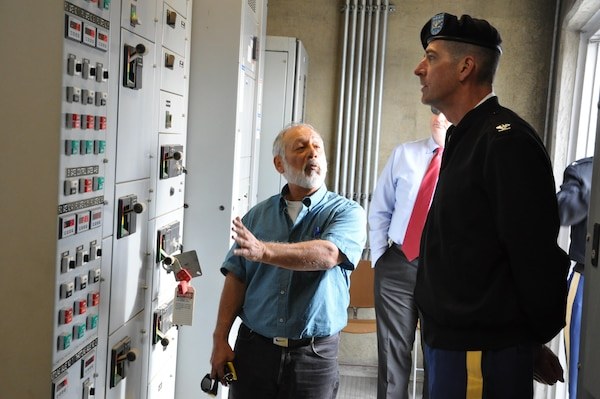 Louis Munoz, dam tender supervisor for the Corps' Los Angeles District, describes the operation of Prado Dam's upgraded regulating outlet gates to South Pacific Division Commander Col. Pete Helmlinger during a Jan. 18 visit to the dam's control tower in Corona, California.