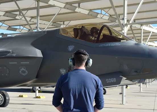 Chad Thomson, 62nd Aircraft Maintenance Unit Lockheed Martin crew chief, stands by to marshal an F-35 Lightning II Jan. 24, 2017, at Luke Air Force Base, Ariz. The 62nd AMU is in the process of integrating Airmen into its maintenance operations. (U.S. Air Force photo by Senior Airman James Hensley)