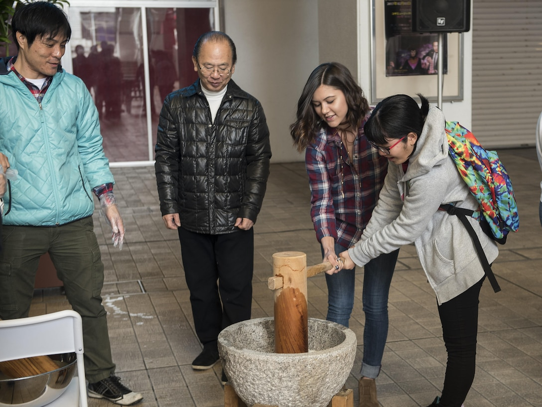 Members of the Kadena Teen Center and Okinawa City junior high school use a wooden mallet to pound rice to make mochi Jan. 21, 2017, at Koza Music City, Okinawa, Japan. The Let's Learn English exchange builds relationships between Okinawan and American teenagers. (U.S. Air Force photo by Airman 1st Class Corey Pettis/Released)