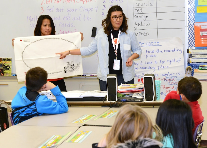 American Red Cross volunteers Cecilia Olivas (center) and Simone Delaflor Evangelista talk to fourth graders at Irving L. Branch Elementary Jan. 19 about the Red Cross' Pillowcase Project. The project encourages third-fifth-graders to learn about emergency preparedness. (U.S. Air Force photo by Kenji Thuloweit)