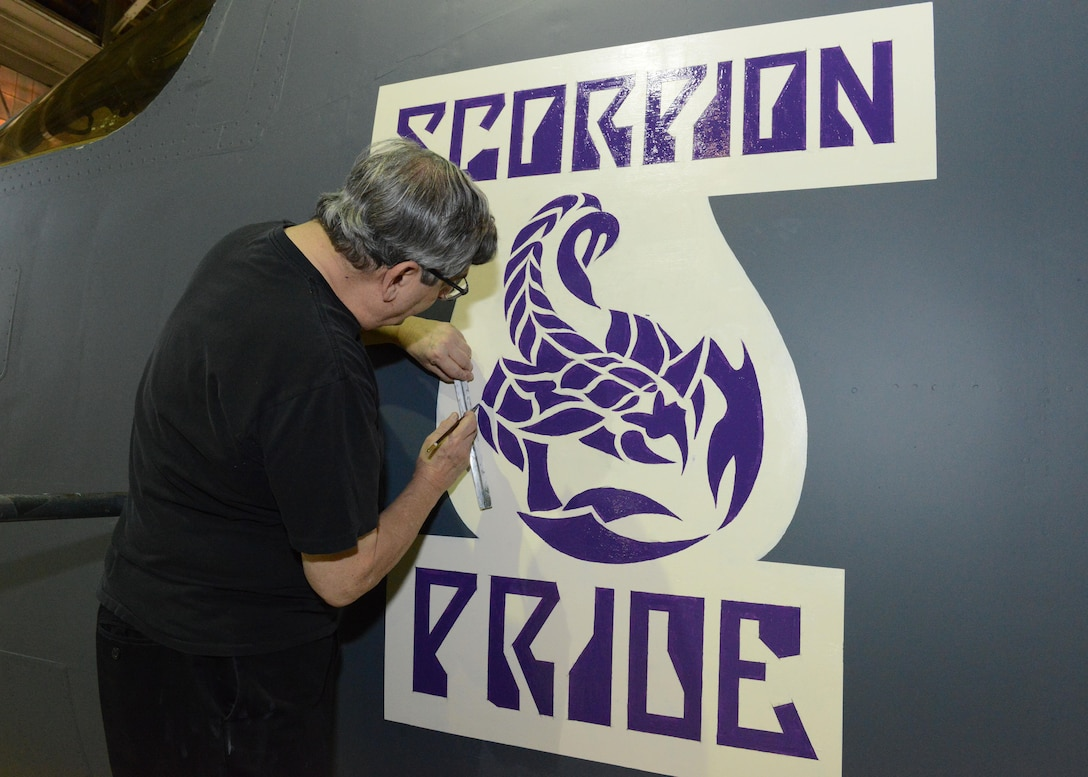Mike Machat, aviation artist, puts the finishing touches on a Desert Junior-Senior High School logo on a 419th Flight Test Squadron B-1 Lancer Dec. 13, 2016. Seniors of DHS Class of 2017 were invited to Hangar 1210 Jan. 19 to tour the plane and take class photos with it. (U.S. Air Force photos by Kenji Thuloweit)