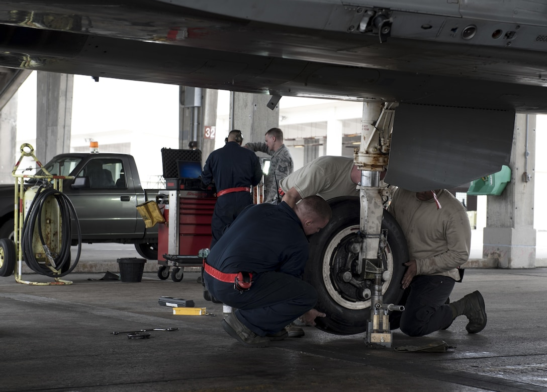 U.S. Air Force 67th Aircraft Maintenance crew chiefs place a new tire onto an F-15 Eagle Jan 10, 2017, at Kadena Air Base, Japan. 67th AMU maintainers are on constant standby to ensure Kadena's F-15 Eagles are able to deploy at a moment's notice. (U.S. Air Force photo by Senior Airman Omari Bernard/Released)