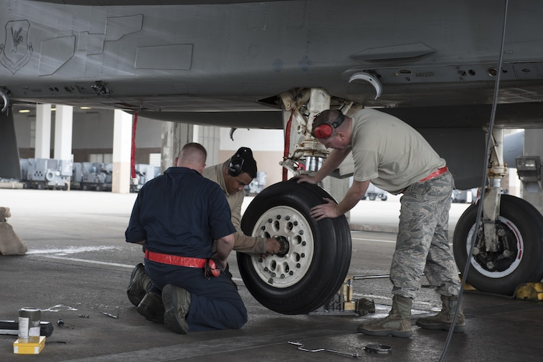 U.S. Air Force 67th Maintenance Unit crew chiefs work together to quickly and safely change the deflated tire of an F-15 Eagle Jan 10, 2017, at Kadena Air Base, Japan. The 67th AMU maintainers work around the clock to ensure Kadena's F-15s remain mission ready to defend and support U.S. and coalition partners' interests throughout the Indo-Asia Pacific region. (U.S. Air Force photo by Senior Airman Omari Bernard/Released)