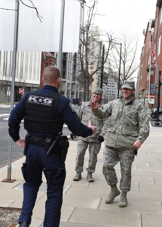 Staff Sgt. David Nichols (right), 193rd Special Operations Security Forces Squadron, and Sgt. Jeff Kopp (left), D.C. Metropolitan Police K-9 Corps, reunite on a D.C. street Jan. 20, 2017, while supporting security missions during the 58th Presidential Inauguration. Formerly serving as Marines, the two men deployed together in 2010 on several combat missions in Afghanistan. (U.S. Air National Guard photo by 2nd Lt. Susan Penning/Released)