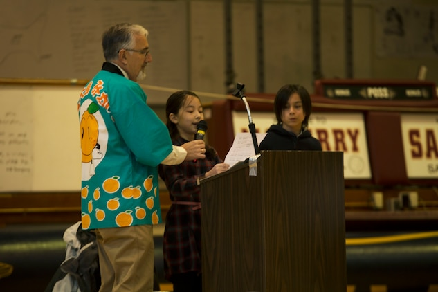 "Hana Cahill, a student at Matthew C. Perry Elementary School, reads a letter of appreciation during the seventh annual mikan presentation at Marine Corps Air Station Iwakuni, Japan, Jan. 19, 2017. The letters were prepared in English and Japanese. Some students made personalized gift bags, and the host nation class showed their gratitude by holding up signs that read ""Thank you for the delicious mikans!"" in Japanese, English and Spanish. Local farmers presented the sweet, easy-to-peel citrus fruit, which is similar to Mandarin oranges, to students expanding their experience of Japanese cultures. (U.S. Marine Corps photo by Lance Cpl. Gabriela Garcia-Herrera)"