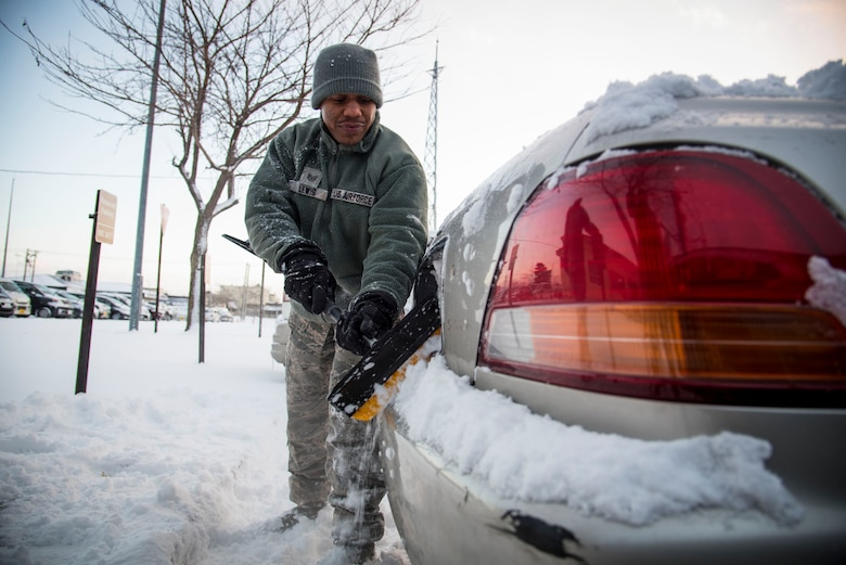 U.S. Air Force Staff Sgt. Dorian Lewis, a 35th Fighter Wing safety technician, removes snow from his vehicle at Misawa Air Base, Japan, Jan. 11, 2017. Base residents are advised to remove from car sides, windows, hood, license plates and the roof of the car, decreasing the dangers of driving during the winter. (U.S. Air Force photo by Airman 1st Class Sadie Colbert)