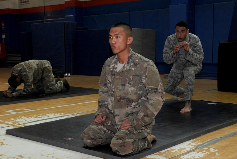 Pfc. Pham Viet, Delta 144th Air Defense Artillery wheel mechanic, left, and Senior Airman Dominic Rivera, 386th Expeditionary Maintenance Squadron craftsman, right, stretch before a fight during an Army combatives tournament at an undisclosed location in Southwest Asia January 22, 2017. Viet and Rivera both trained daily together to prepare themselves for the mixed martial arts competition. (U.S. Air Force photo/Tech. Sgt. Kenneth McCann)