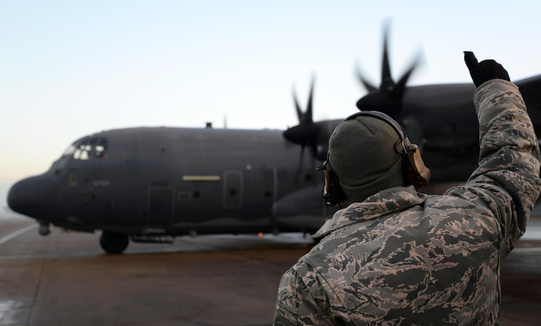 A U.S. Air Force crewchief, assigned to the 352d Special Operations Aircraft Maintenance Squadron, gives a thumbs up to an MC-130J Commando II from the 67th Special Operations Squdron Jan. 17, 2016, as it taxis on the flight line on RAF Mildenhall, England. Prior to takeoff the aircraft underwent de-icing procedures to ensure free movement of the primary and secondary flight controls. (U.S. Air Force photo by Senior Airman Justine Rho)
