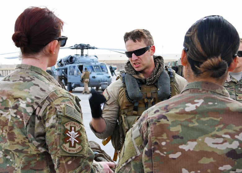 U.S. Navy Petty Officer 2nd Class Nick Flynn, a naval aircrewman assigned to Helicopter Sea Combat Squadron 26, gives a flight safety briefing to members of the 379th Expeditionary Medical Operations Squadron mobile field surgical and expeditionary critical care teams at Al Udeid Air Base, Qatar, Jan. 23, 2016. The medical team departed onboard two SH-60 Seahawks to join Royal Navy forces aboard the HMS Ocean for a coalition exercise where they will simulate providing care to casualties at sea. (U.S. Air Force photo by Senior Airman Miles Wilson)