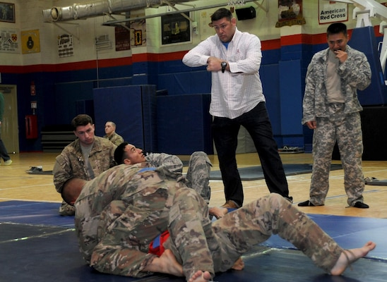 Master Sgt. Royce Kerbow, the 386th Air Expeditionary Wing command post superintendent, coaches his students during an Army combatives tournament match at an undisclosed location in Southwest Asia Jan. 22, 2017. Kerbow prepared his students with daily Brazilian jujitsu workouts. (U.S. Air Force photo/Tech. Sgt. Kenneth McCann)