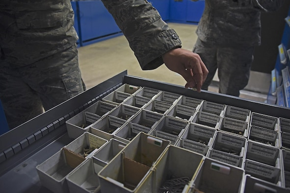 Senior Airman Nick Monroe, 92nd Maintenance Squadron periodic inspection support section journeyman, conducts daily bench stock program duties Jan. 20, 2017, at Fairchild Air Force Base, Wash. With thousands of individual fasteners in hundreds of variations, the process of updating bench stock inventory could take eight hours and since receiving the RoboCrib, the process has been reduced to less than 30 minutes. (U.S. Air Force photo/Senior Airman Mackenzie Richardson)