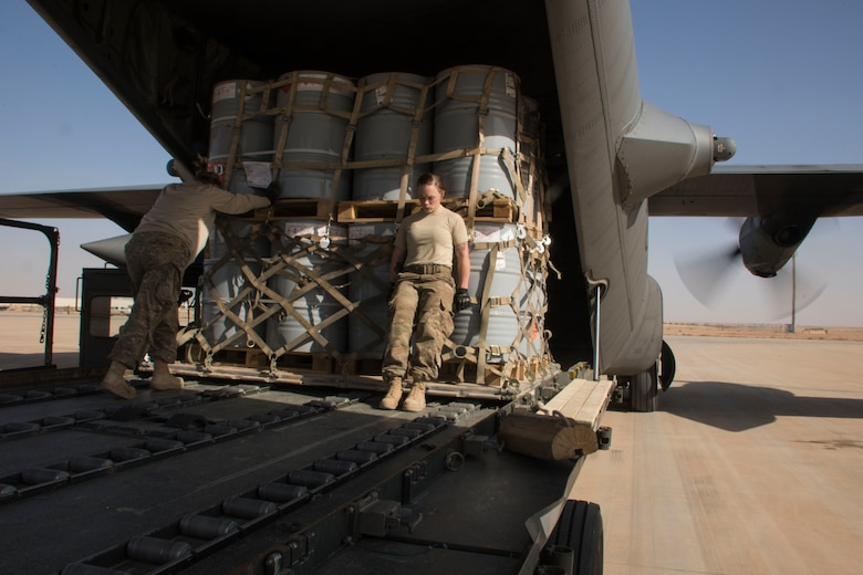 Two aerial porters from the 870th Air Expeditionary Squadron push a pallet of supplies into the cargo area of a C-130H Hercules at Al Asad Air Base, Iraq, Jan. 9, 2017. The diverse cargo handled by these aerial porters can include rations, vehicles, rockets, or many other important items. (U.S. Air Force photo/Senior Airman Andrew Park)