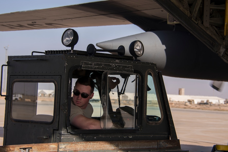 Senior Airman Christian Hall, an 870th Air Expeditionary Squadron aerial porter, watches as a pallet of supplies is offloaded from the K-loader he is driving at Al Asad Air Base, Iraq, Jan. 9, 2017. 870th AEAS aerial porters are required to be able to operate a variety of vehicles and machinery around the aerial port. (U.S. Air Force photo/Senior Airman Andrew Park)