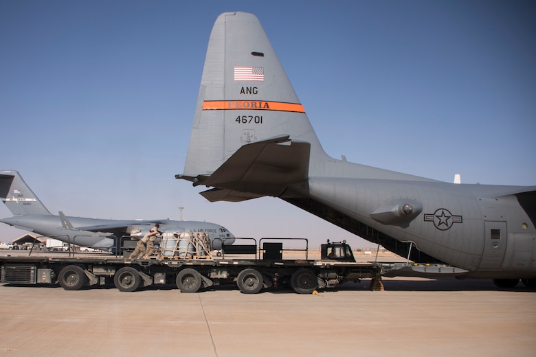 Aerial porters from the 870th Air Expeditionary Squadron push a pallet of supplies from a K-loader into the back of a C-130H Hercules at Al Asad Air Base, Iraq, Jan. 9, 2017. Aerial porters are responsible for loading and unloading aircraft and moving cargo around the cargo yard. (U.S. Air Force photo/Senior Airman Andrew Park)