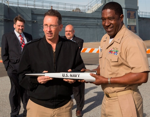 """DAHLGREN, Va. - Rear Admiral David Hahn, chief of naval research, and Capt. Godfrey """"Gus"""" Weekes, NSWCDD commanding officer, hold an electromagnetic railgun projectile during Hahn's visit to NSWCDD, Jan. 12. The admiral led his Office of Naval Research (ONR) delegation to see new and emerging ONR sponsored technologies developed at NSWCDD, including directed energy and the electromagnetic railgun. They also watched engineers fire a hypervelocity projectile from a 5-inch, 62-caliber open mount gun at the Potomac River Test Range. (U.S. Navy photo by Ryan DeShazo/Released)"""