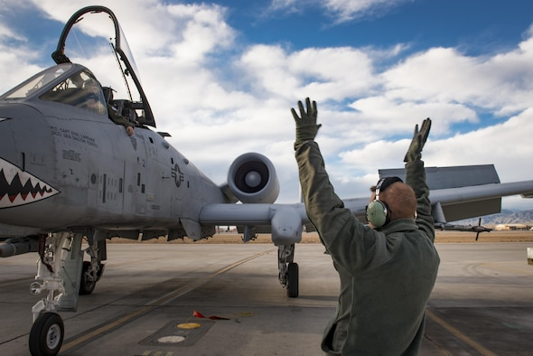 Senior Airman Cody Campbell, 74th Aircraft Maintenance Unit crew chief, marshals an A-10C Thunderbolt II to a parking spot during Green Flag-West 17-03, Jan. 23, 2017, at Nellis Air Force Base, Nev. GFW is an air-land integration combat training exercise, which hosted 12 A-10s from Moody Air Force Base, Ga. Accompanying the aircraft were 130 maintenance personnel who worked around the clock to launch 18 sorties per day. (U.S. Air Force photo by Staff Sgt. Ryan Callaghan)