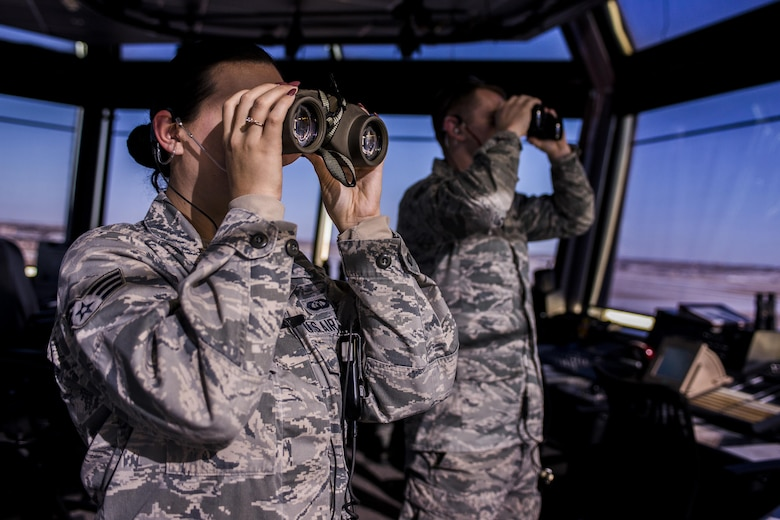 Two 27th Special Operations Support Squadron Air Traffic Controllers look through binoculars toward incoming aircraft Jan. 6, 2017, at Cannon Air Force Base, N.M. The controllers in the tower work directly with Radar Approach Control to ensure all aircraft launch, fly and arrive safely. (U.S. Air Force photo by Senior Airman Luke Kitterman/Released)