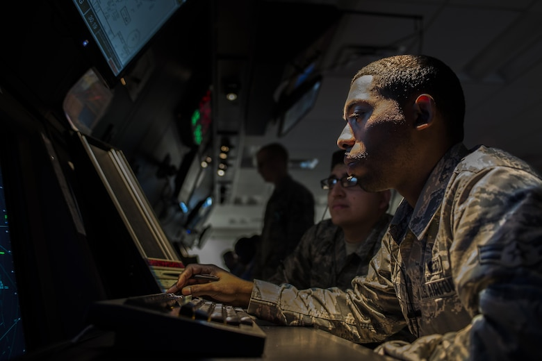 Two 27th Special Operations Support Squadron Air Traffic Controllers assigned to Radar Approach Control view a display screen showing aircraft in the surrounding airspace Jan. 6, 2017, at Cannon Air Force Base, N.M. The RAPCON team is responsible for any air craft in their airspace including non-military flights coming from nearby air traffic facilities, also known as overflights. (U.S. Air Force photo by Senior Airman Luke Kitterman/Released)