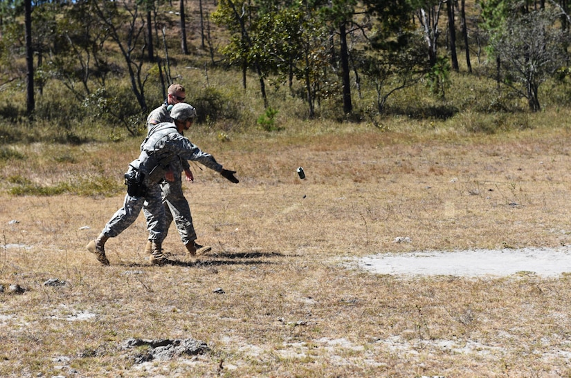 A service member assigned to Joint Task Force- Bravo's Joint Security Forces throws a smoke canister that will mark the landing zone for a UH-60 helicopter as part of a joint Medical Evacuation training exercise between JSF and the 1st Battalion, 228th Aviation Regiment, near Soto Cano Air Base, Honduras, Jan. 18, 2017.