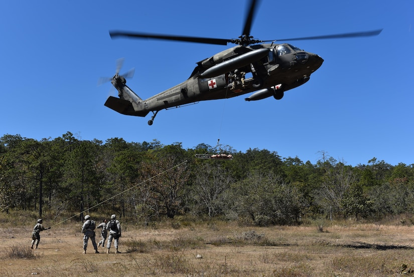 A team comprised of Joint Security Forces personnel and 1st Battalion, 228th Aviation regiment flight paramedics prepares to hoist a mannequin onto a helicopter during a joint Medical Evacuation training, near Soto Cano Air Base, Honduras, Jan. 18, 2017. The training exercise increased coordination between ground forces and flight crews to securely and safely perform an emergency medical evacuation in preparations for a real life event.