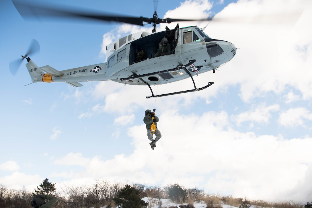 Tech. Sgt. Michael Wright, a 459th Airlift Squadron special mission aviator evaluator, holds onto the cable as Master Sgt. Antonio Gueits, a 374th Operation Group resource adviser, is hoisted into a UH-1N Huey at a drop zone near Mount Fuji, Japan, Jan. 13, 2017. During the scenario, aircrew performed an alternate insertion of crew members, hoist insertion and extraction from 25-35 feet above ground and proper landing and takeoff techniques throughout various landing zones. (U.S. Air Force photo/Staff Sgt. David Owsianka)
