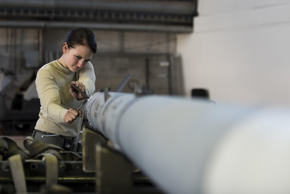Airman 1st Class Gina Herringer-Koblack, 52nd Aircraft Maintenance Squadron tactical aircraft weapons system specialist, prepares an inert weapon for loading during the annual weapons load competition in Hangar One at Spangdahlem Air Base, Germany, Jan. 20, 2016. The competition featured two teams competing for the wing's best load crew. Additionally, the winning team's completion time will be compared to other squadrons in the Major Command to determine the best load crew in United States Air Forces in Europe. The wing winner will be announced at the Maintenance Professional of the Year banquet March 10, 2016. (U.S. Air Force photo by Airman 1st Class Preston Cherry)