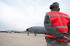 Senior Airman Jaramie York, 459th Aircraft Maintenance Squadron maintainer, awaits approval to marshal a KC-135R Stratotanker down the runway at Joint Base Andrews, Md., Dec. 13, 2016. The aircraft burns approximately 10,000 pounds of fuel during a typical four-hour mission when its four engines are running. (U.S. Air Force photo by Staff Sgt. Joe Yanik)