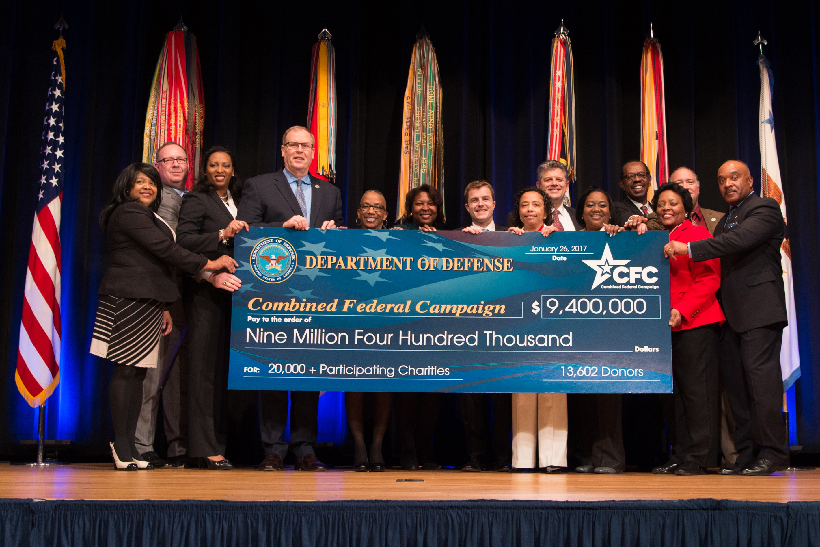 Deputy Defense Secretary Bob Work poses for a photo holding the check