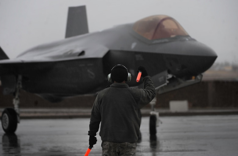 A crew chief, assigned to the 34th Fighter Squadron, Hill Air Force Base, Utah, marshals an F-35A Lightning II after landing on Nellis Air Force Base, Nev., Jan. 21, 2017. The F-35A will be participating in Red Flag 17-1, making it the first iteration to incorporate the fifth generation fighter. (U.S. Air Force photo by Airman 1st Class Kevin Tanenbaum/Released)