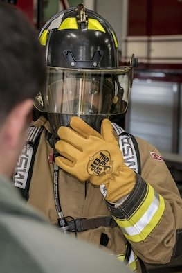 U.S. Air Force Airman 1st Class Daronda Marsh, right, a customer support technician with the 35th Force Support Squadron, straps on and checks the seal of her self-contained breathing apparatus, or SCBA, as Airman 1st Class Thomas Ulrich, left, a firefighter with the 35th Civil Engineer Squadron, walks her through the process at Misawa Air Base, Japan, Jan. 26, 2017. Marsh jumped at the opportunity to join five other Airmen who took part in Misawa's first-ever career field exchange and shadow program. The initiative affords service members of all ranks from across the installation an opportunity to live a day in another's boots. (U.S. Air Force photo by Staff Sgt. Benjamin W. Stratton)