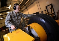 U.S. Air Force Senior Airman Tyler Hyatt, 100th Maintenance Squadron aero repair journeyman, places a tire into a bead breaker Jan. 20, 2017, on RAF Mildenhall, England. The bead breaker breaks two beads which connect the tire and wheel. (U.S. Air Force photo by Senior Airman Christine Halan)