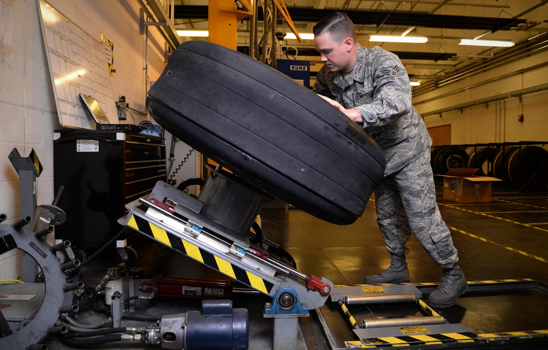 U.S. Air Force Senior Airman Tyler Hyatt, 100th Maintenance Squadron aero repair journeyman, places a wheel and tire assembly onto a wheel clamp Jan. 20, 2017, on RAF Mildenhall, England. The wheel clamp ensure proper disassembly of the wheel and tire. (U.S. Air Force photo by Senior Airman Christine Halan)