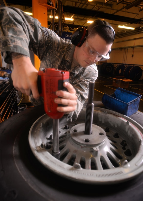 U.S. Air Force Senior Airman Tyler Hyatt, 100th Maintenance Squadron aero repair journeyman, disassembles a wheel and tire assembly with an pneumatic wrench Jan. 20, 2017, on RAF Mildenhall, England. The wheel clamp ensures proper disassembly of the wheel and tire. (U.S. Air Force photo by Senior Airman Christine Halan)