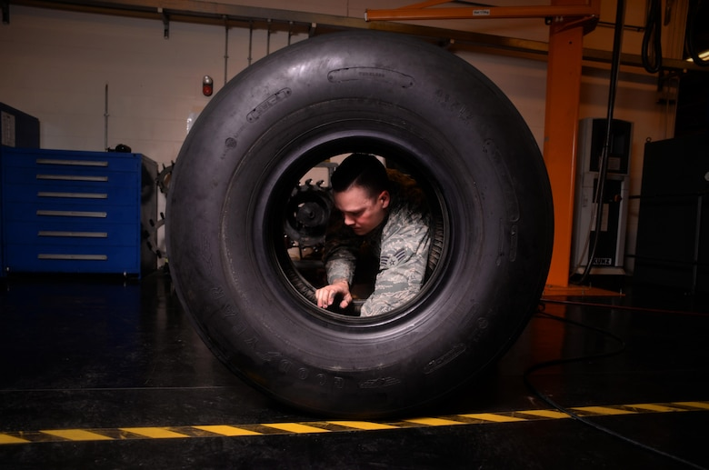 U.S. Air Force Senior Airman Tyler Hyatt, 100th Maintenance Squadron aero repair journeyman, removes a phenolic ring from a tire after separating the wheel and tire assembly Jan. 20, 2017, on RAF Mildenhall, England. The ring helps stop the two pieces from grinding metal on metal. (U.S. Air Force photo by Senior Airman Christine Halan)